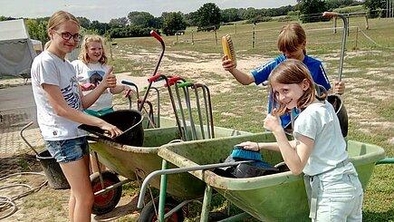 Kinder helfen bei der Pferde- und Koppelpflege.