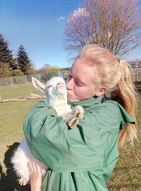 Lehrling Sarah mit einer der Ziegenschützlinge.
