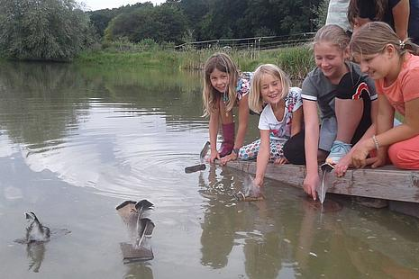 Kinder basteln Schiffchen und lassen sie schwimmen