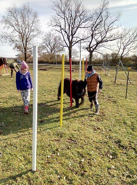 Kinder mit Pony auf dem Pferdeparcours